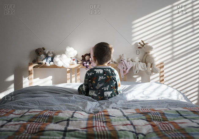 Rear view of boy sitting on bed at home