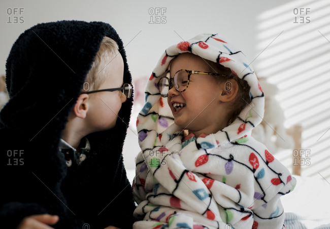 Happy siblings wearing warm clothing looking at each other while sitting in bedroom