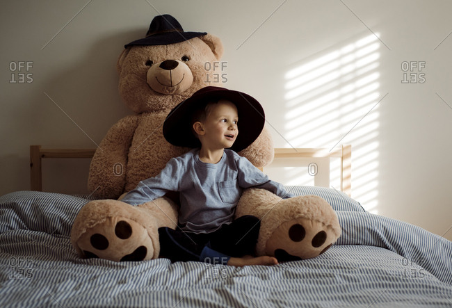 Boy with teddy bear sitting on bed at home