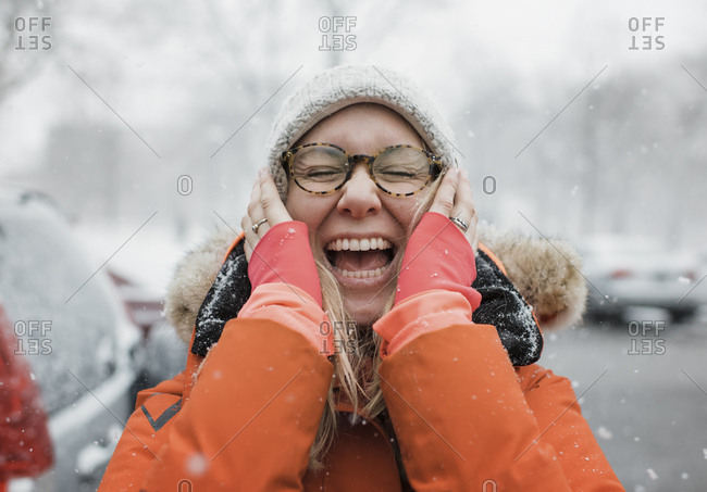 Happy woman with hands on chin screaming while standing on road during snowfall