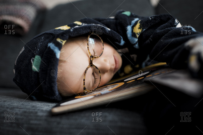 Boy in hooded shirt sleeping on bed at home