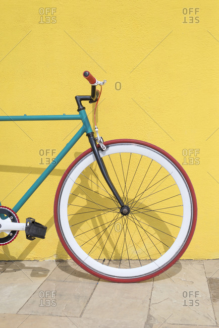 Bicycle parked against yellow wall at sidewalk in city