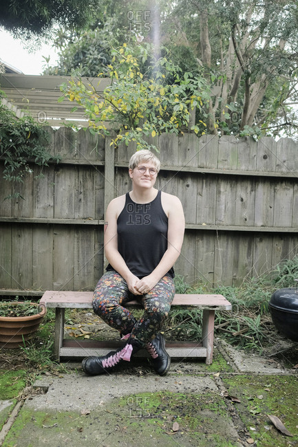 Full length of trans woman sitting on bench at backyard