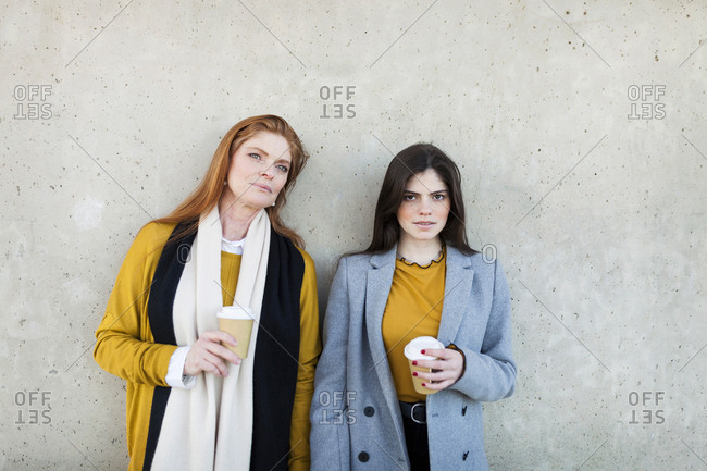 Portrait of daughter with disposable cup standing by mother against wall in city