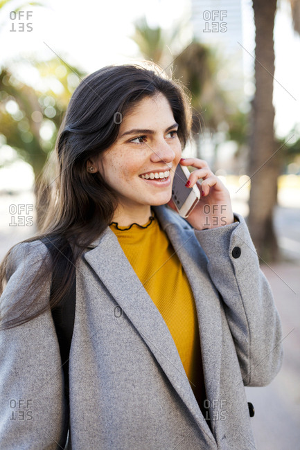 Smiling young woman answering smart phone while wearing overcoat in city