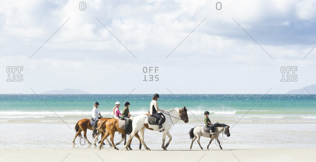 North Island, New Zealand - August 20, 2012: Several young people are riding their horses along a sandy beach with a turquoise blue sea behind them