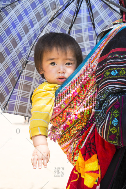 Sapa, Vietnam - May 7, 2015: A cute baby being carried on the back of its mother in a brightly colored bag