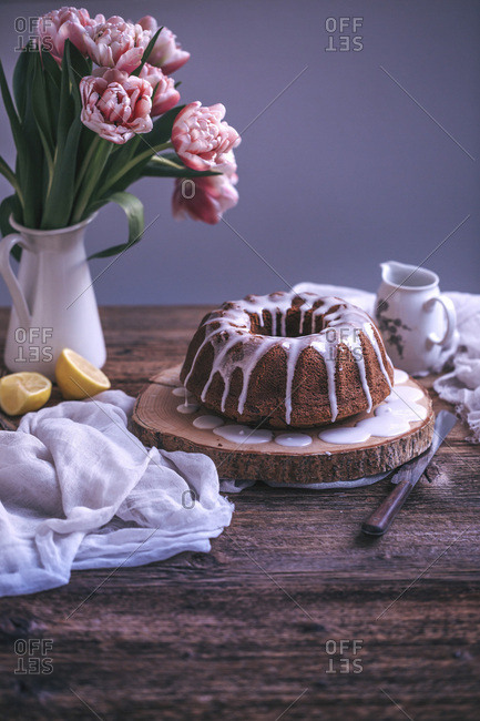 Bundt cake with lemon glaze drizzle on a rustic wooden table
