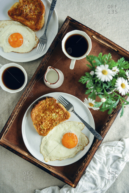 Easy French toast served with a fried egg on the side on a white plate, a cup of coffee, milk and spring flowers in a wooden tray photographed from top view Another plate with a french toast and an egg and another coffee cup accompany