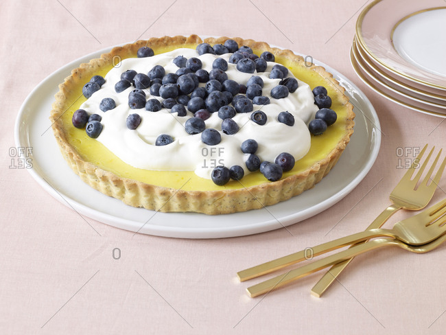 Side view of lemon tart with fresh blueberries and cream, pink and gold plates, gold forks on pink linen