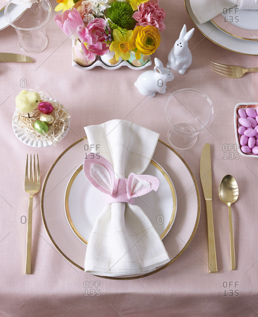 Place setting at Easter meal with shades of pink, spring flowers and bunny salt and pepper