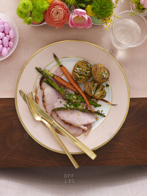 Place setting with Easter ham and vegetables on formal pink plate and gold flatware