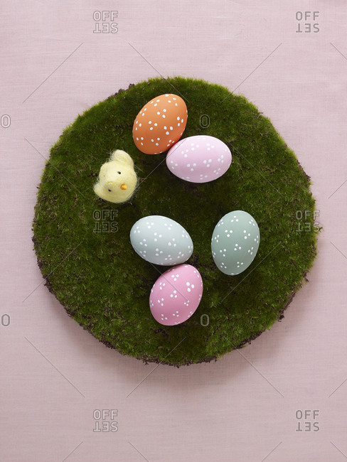 Dot decorated multicolor Easter eggs on moss circle with pink background