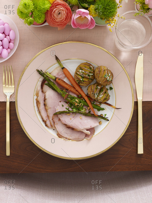 Single place setting at Easter table with sliced ham and vegetables and flowers