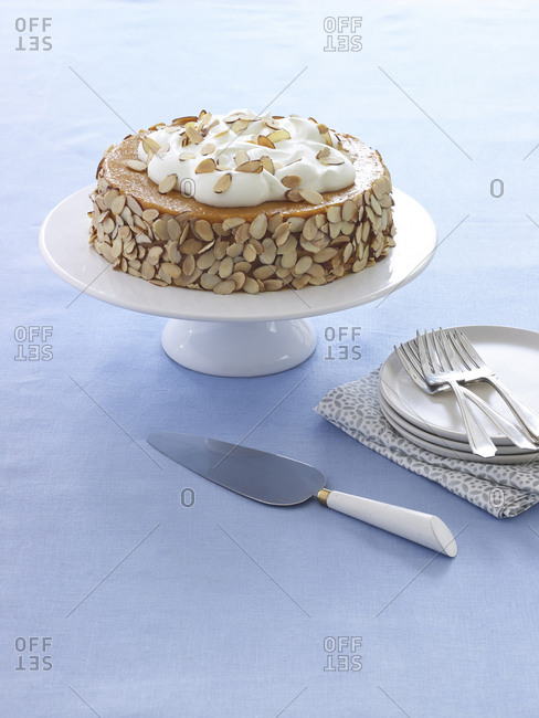 Passover cake with almonds and cream on cake stand with blue linen and plates