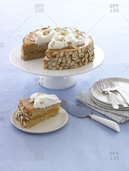 Passover cake with almonds and cream on cake stand with slice taken out on blue linen