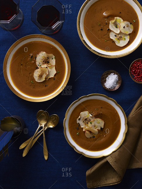 Three gold rimmed bowls of pumpkin kuri soup with crisp apple garnish served on rich blue linen with gold flatware