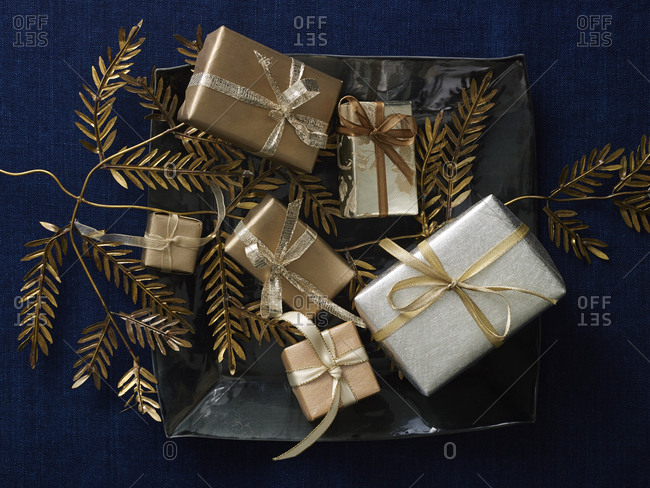 Six small gold wrapped gifts with golden fronds and a black ceramic tray on dark blue