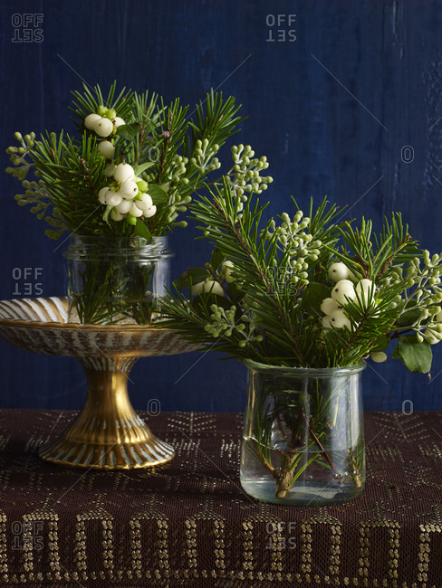 Small holiday flower arrangements with winter berries and evergreen in glass vessels on gold and blue