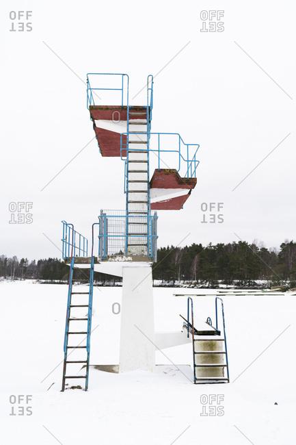 A rusty swim tower in the winter taiga