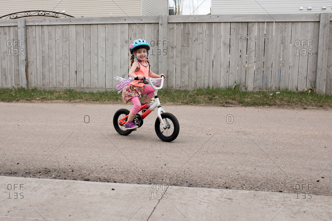 Smiling girl riding bicycle with streamer decorations