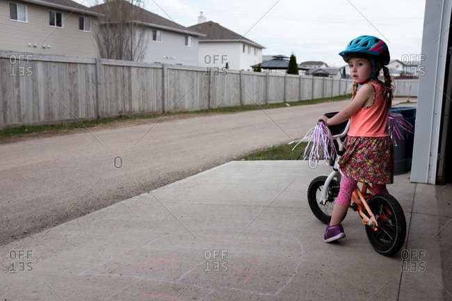 Girl sitting on parked bike in driveway