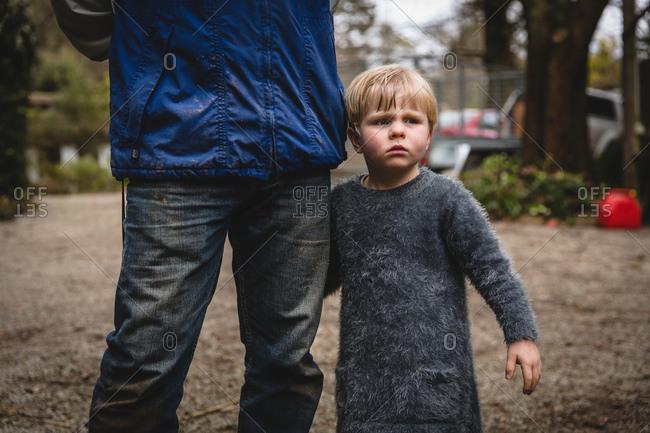 Boy holding father's leg