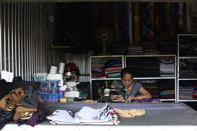 Central Highlands, Vietnam - January 9, 2018: Traditional vietnamese female sewing clothes at a warehouse