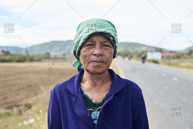Central Highlands, Vietnam - January 10, 2018: Minority ethnic vietnamese female posing at camera on the middle of the road