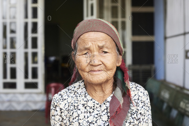 Central Highlands, Vietnam - January 11, 2018: Portrait of minority ethnic vietnamese senior lady with grey hair looking at camera