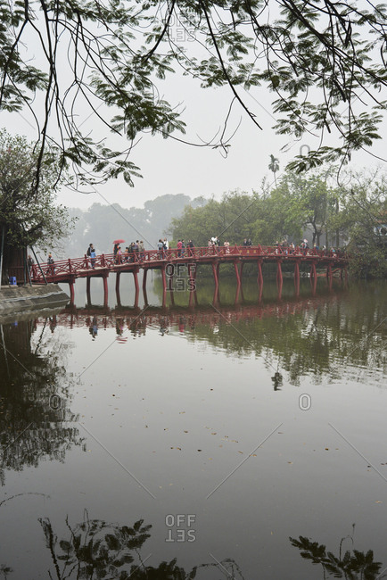 Hanoi, Vietnam - February 24, 2018: People crossing the red bridge landmark located on the lake