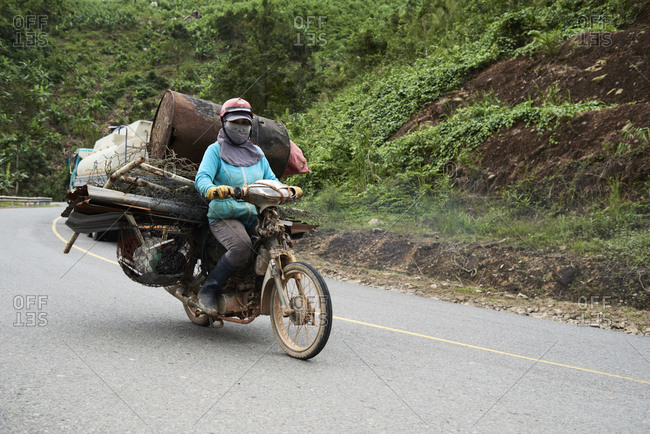 Central Highlands, Vietnam - January 11, 2018: Senior lady driving a motorbike carrying garbage through the mountains