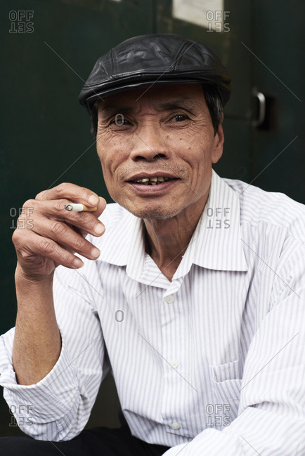 Hanoi, Vietnam - February 28, 2018: Portrait of senior vietnamese male smoking on the street