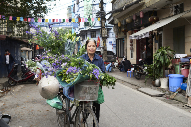 Hanoi, Vietnam - February 28, 2018: Senior street vendor selling flowers on a bicycle