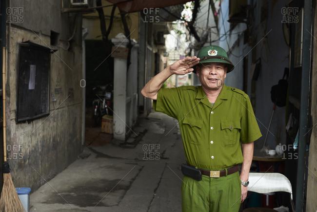 Hanoi, Vietnam - February 28, 2018: Portrait of senior vietnamese soldier greeting with hand over head