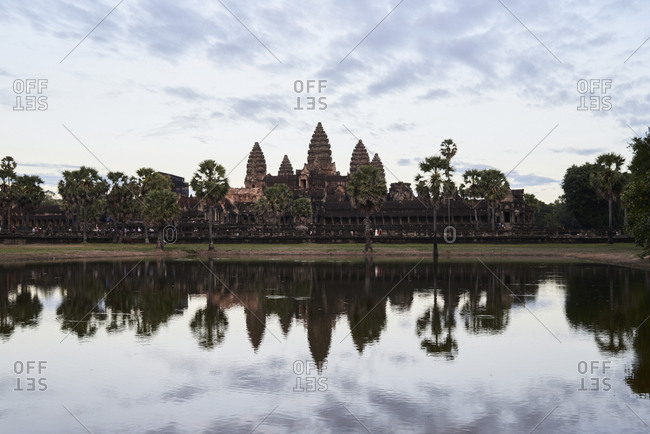 Cambodian landmark Angkor Wat temple with reflection in water at sunset, Siem Reap, Cambodia