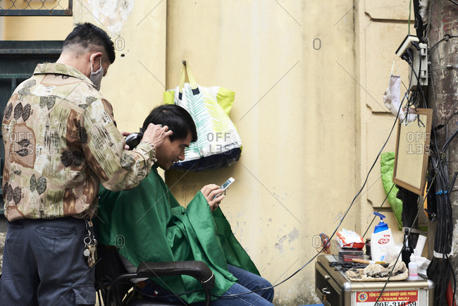 Hanoi, Vietnam - February 28, 2018: Barber shop on the street attending a client checking smartphone