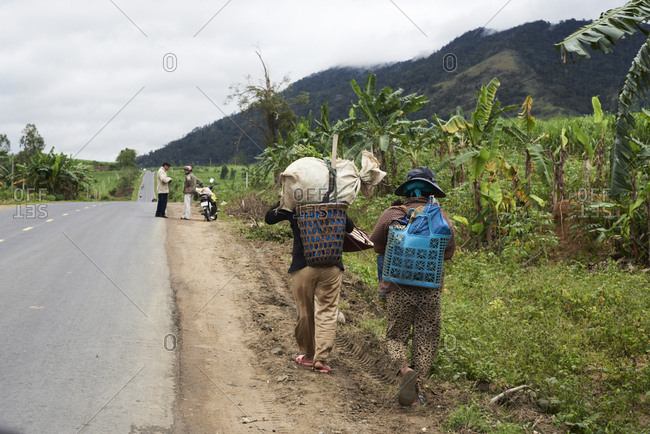 Traditional vietnamese farmers carrying goods on the road at the mountains in central highlands, Vietnam