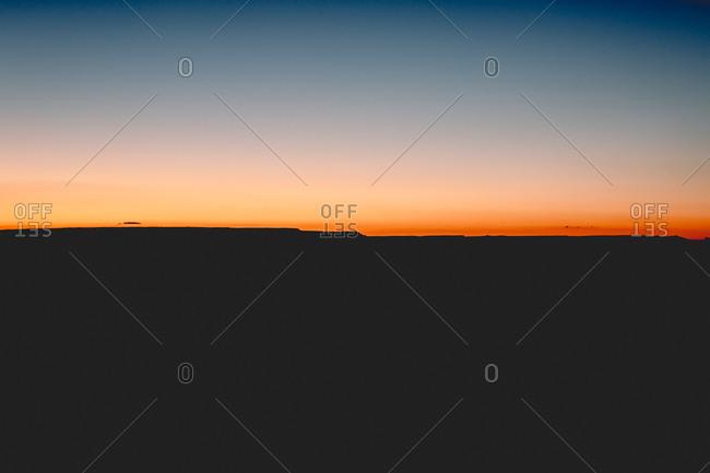 Sun below horizon setting sky ablaze