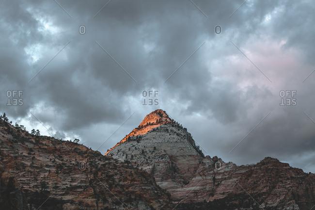 Sun lighting apex of sandstone peak