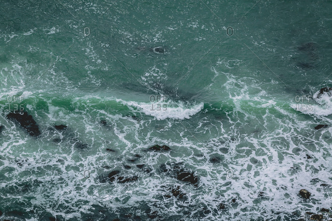 Aerial view of waves crashing against rocky shoreline
