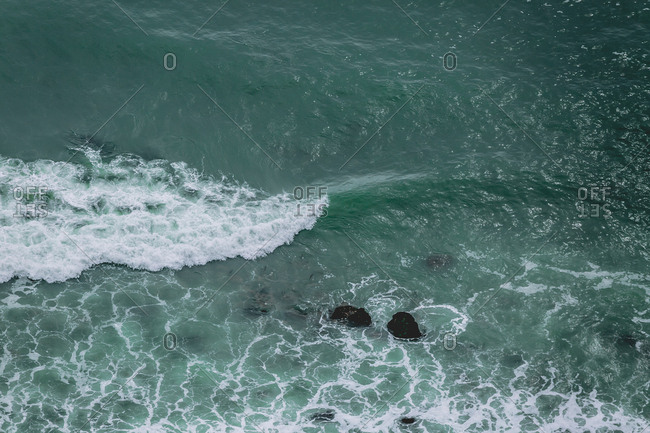 Aerial view of wave breaking onto rocks on coast