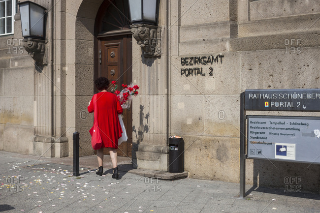 Berlin, Germany - August 15, 2015: A woman in red carrying red flowers