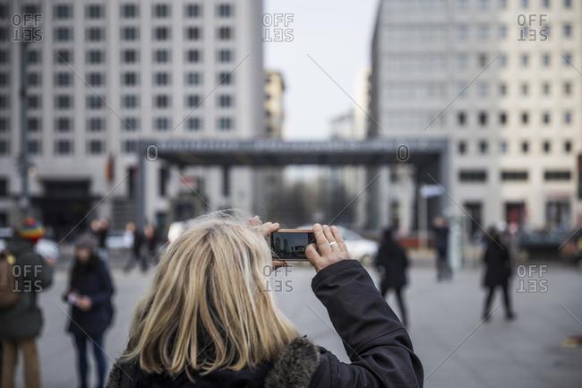 A tourist takes a photograph in Potsdamer Platz, Berlin, Germany
