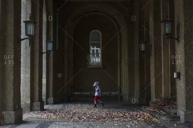 Berlin, Germany - August 15, 2015: A young boy walks over strewn confetti