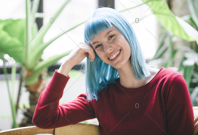 Portrait of young stylish woman with blue dyed hair smiling