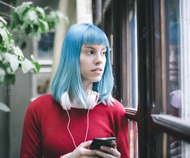 Stylish girl with blue colored hair and headphones listens to music from her smart phone