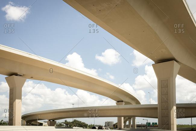 Vehicles traveling under overpass along multi lane highway