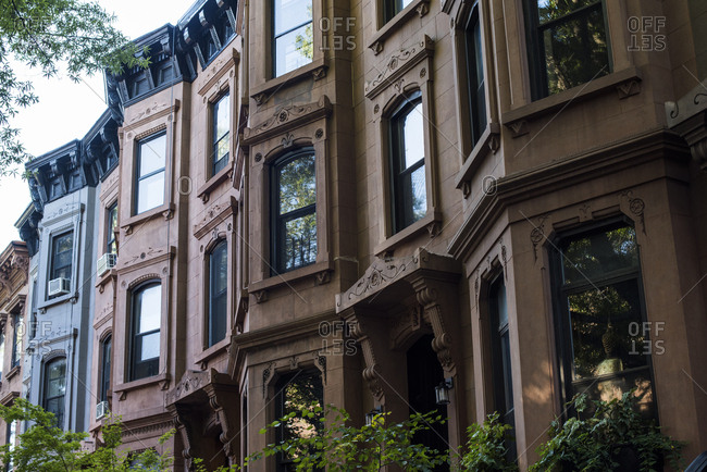 Looking up at facades of row of Brownstones in Brooklyn, New York