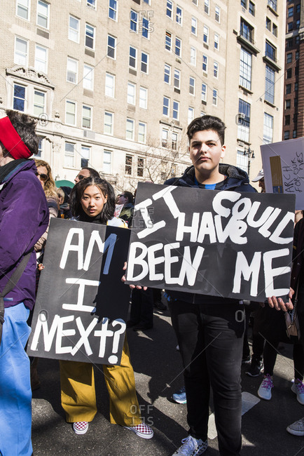 New York City, NY, USA - March 24, 2018: Young boy and girl displaying hand written signs against gun violence at March For Our Lives 2018 demonstration